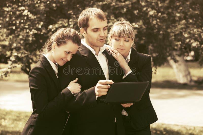 使用膝上型计算机的年轻商人在城市公园 免版税库存图片