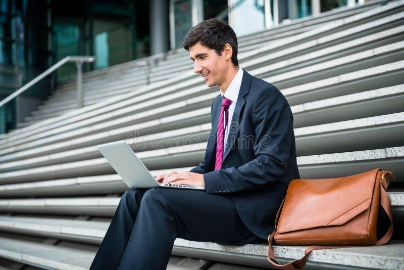 使用膝上型计算机的年轻商人,当坐下户外时 免版税库存照片