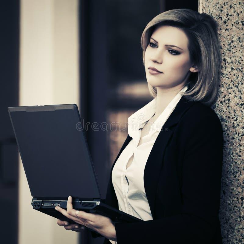 使用膝上型计算机的年轻女商人在办公楼 免版税库存图片