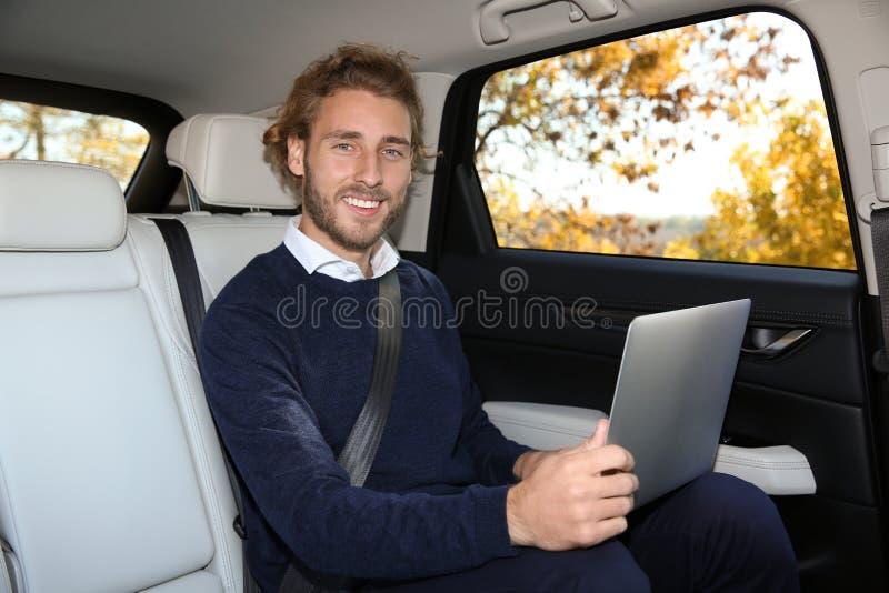 使用膝上型计算机的年轻帅哥在后座 免版税库存图片