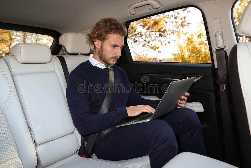 使用膝上型计算机的年轻帅哥在后座 库存图片