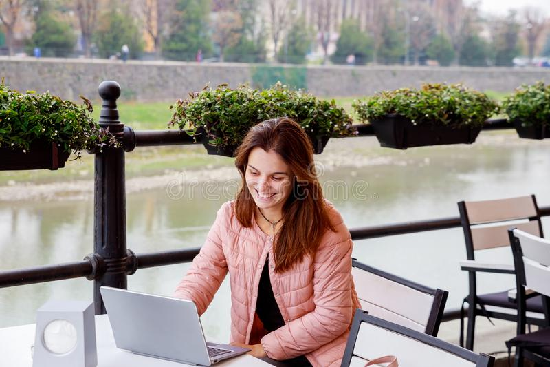 使用膝上型计算机的年轻微笑的女孩为工作,当坐在室外咖啡馆,学习在公园和使用现代膝上型计算机的学生在晴朗时 库存图片