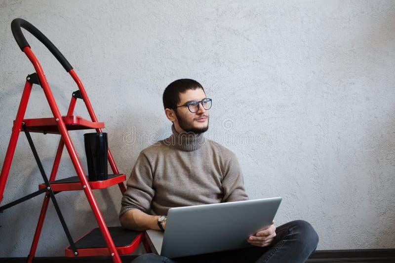 使用膝上型计算机的年轻想法的有胡子的行家,在红色金属台阶附近的白色背景 库存图片