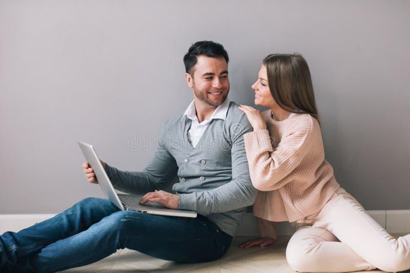 使用膝上型计算机的年轻愉快的夫妇坐地板 免版税图库摄影