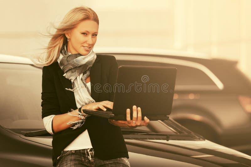 使用膝上型计算机的年轻时装业妇女在她的在停车处的汽车旁边 免版税库存照片