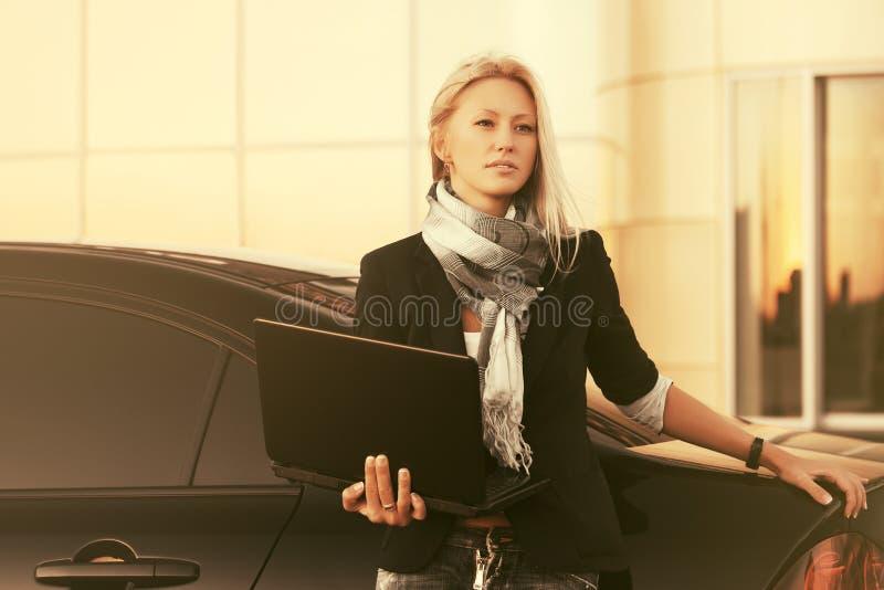 使用膝上型计算机的年轻时装业妇女在她的汽车旁边 库存图片