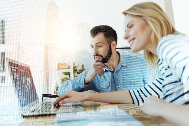 使用膝上型计算机的年轻透视工作者夫妇和看起来周道地 免版税库存照片