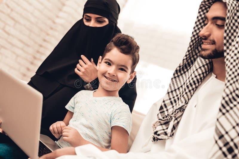 使用膝上型计算机的年轻阿拉伯家庭在沙发在家 免版税库存照片
