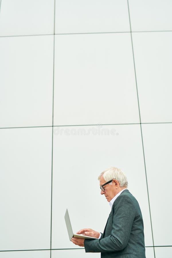 使用膝上型计算机的年迈的企业家在大厦附近 库存图片