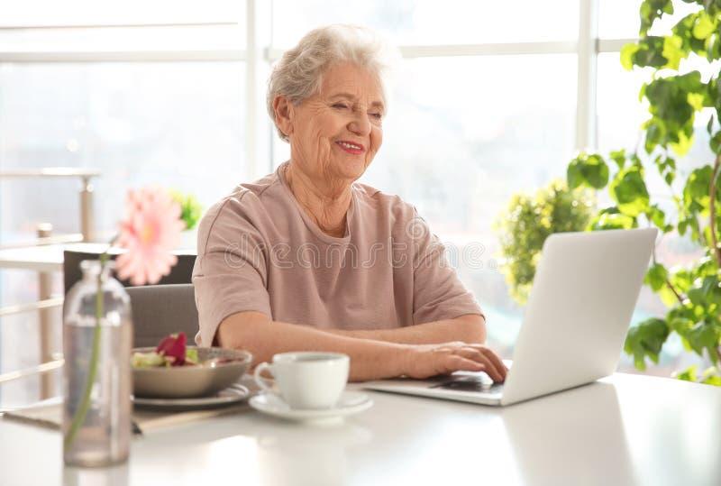 使用膝上型计算机的年长妇女,当食用早餐时 库存图片