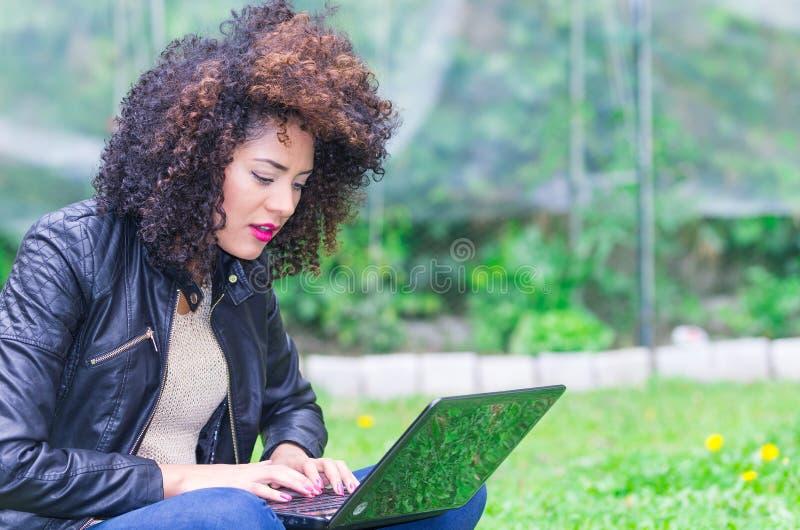 使用膝上型计算机的异乎寻常的美丽的女孩在 免版税库存图片