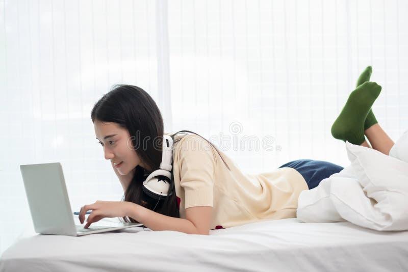 使用膝上型计算机的微笑的亚洲妇女,当说谎在她的床、启发、创造性、舒适和人概念上时 库存照片