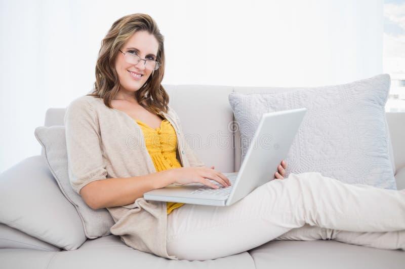 使用膝上型计算机的微笑的华美的模型在舒适沙发 库存照片