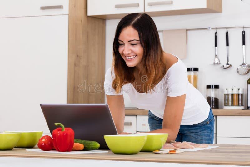 使用膝上型计算机的微笑的妇女在厨房 图库摄影