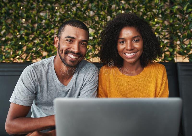 使用膝上型计算机的微笑的年轻夫妇 免版税库存照片