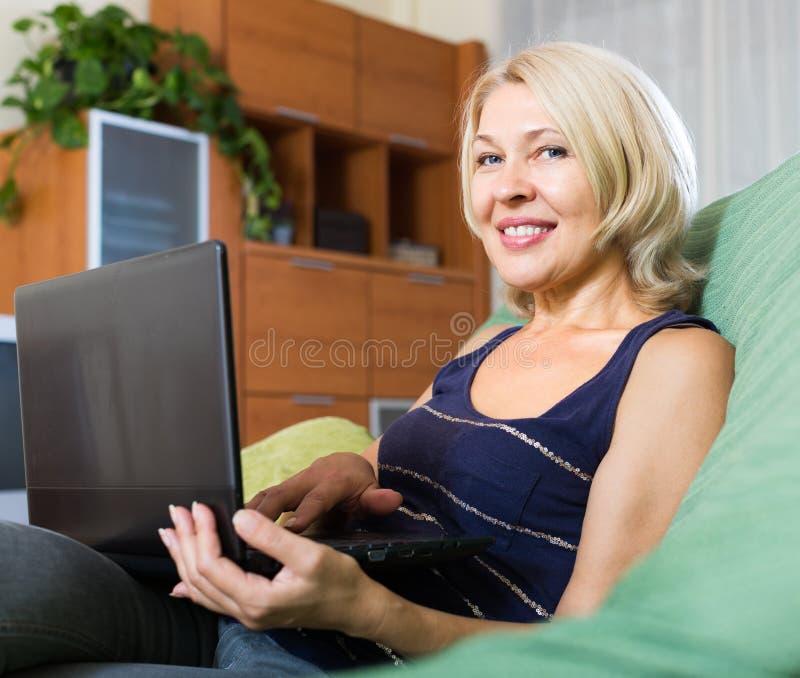 使用膝上型计算机的微笑的成熟妇女 免版税库存照片