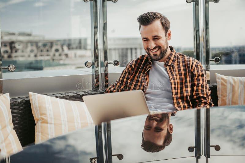 使用膝上型计算机的微笑的有胡子的人在室外咖啡馆 库存图片