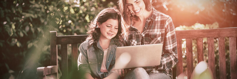 使用膝上型计算机的微笑的母亲和女儿,当坐长木凳时 免版税库存照片
