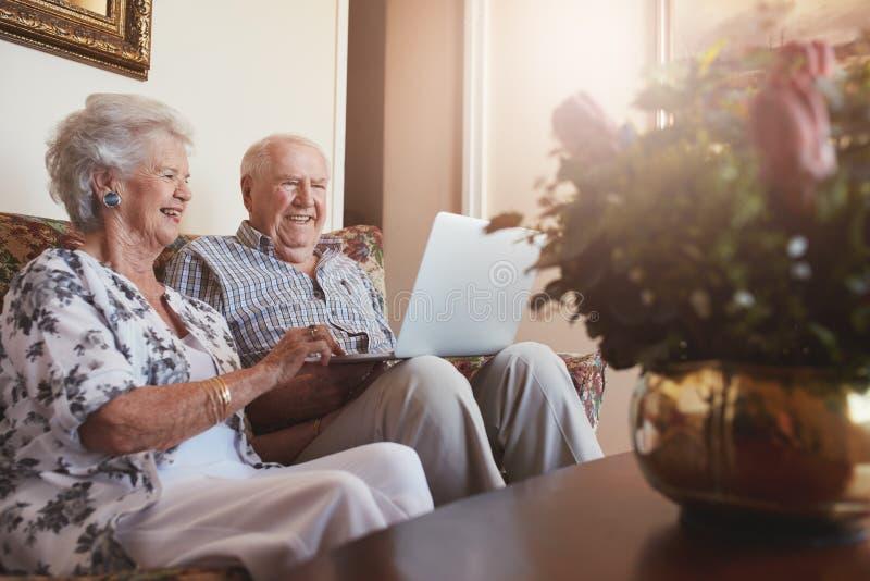 使用膝上型计算机的微笑的资深夫妇在家 免版税库存照片