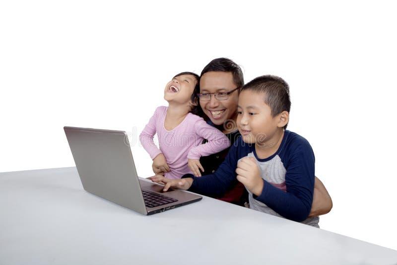 使用膝上型计算机的快乐的孩子和爸爸 免版税图库摄影