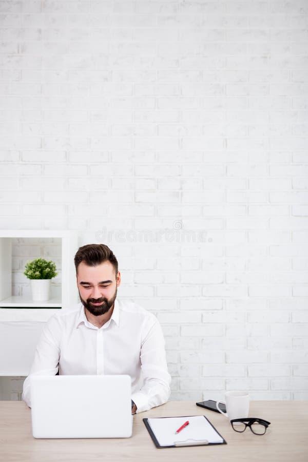 使用膝上型计算机的快乐的有胡子的商人画象在办公室-在白色砖墙的拷贝空间 库存图片
