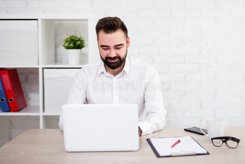 使用膝上型计算机的快乐的有胡子的商人画象在办公室 库存照片