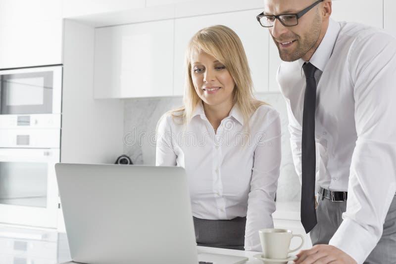 使用膝上型计算机的愉快的中间成人企业夫妇在厨台 图库摄影