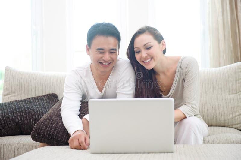 使用膝上型计算机的愉快的亚洲夫妇 图库摄影