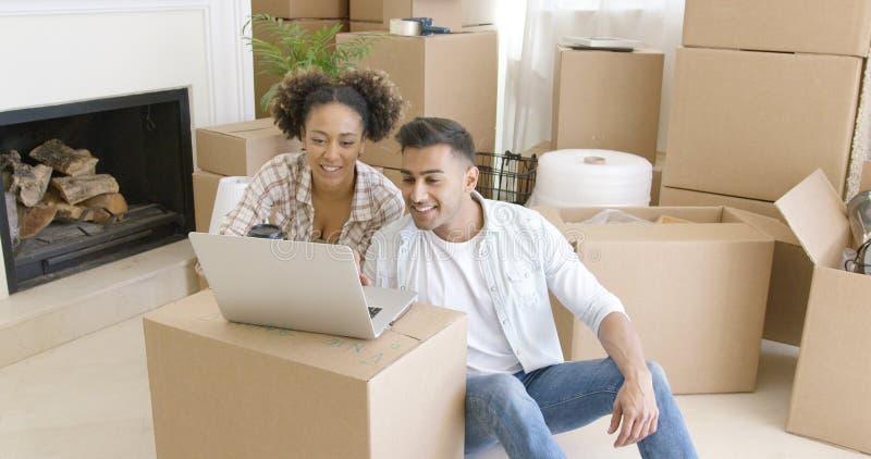 使用膝上型计算机的愉快的夫妇在他们新的公寓 库存照片