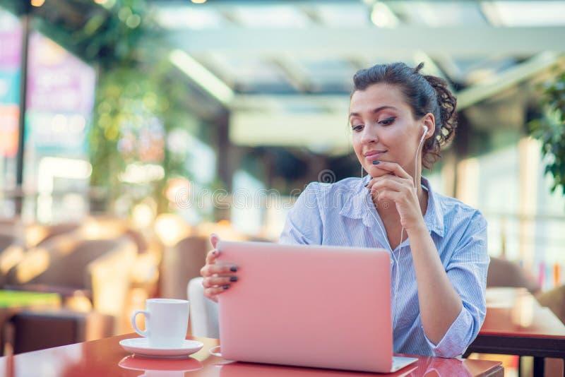 使用膝上型计算机的愉快的妇女的图象,当坐在咖啡馆时 坐在咖啡馆和研究膝上型计算机的年轻女人 免版税图库摄影