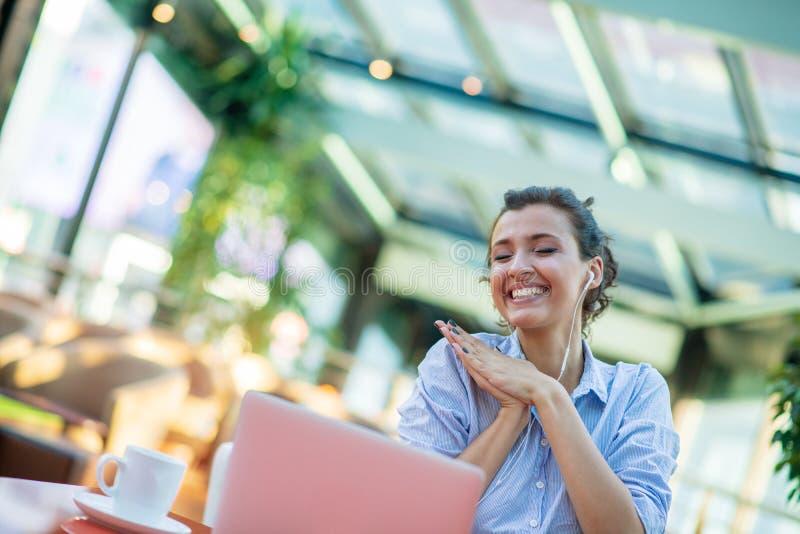使用膝上型计算机的愉快的妇女的图象,当坐在咖啡馆时 坐在咖啡馆和研究膝上型计算机的年轻女人 库存图片