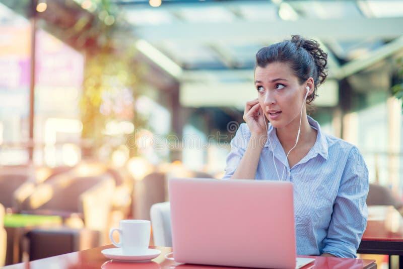 使用膝上型计算机的愉快的妇女的图象,当坐在咖啡馆时 坐在咖啡馆和研究膝上型计算机的年轻女人 免版税库存照片