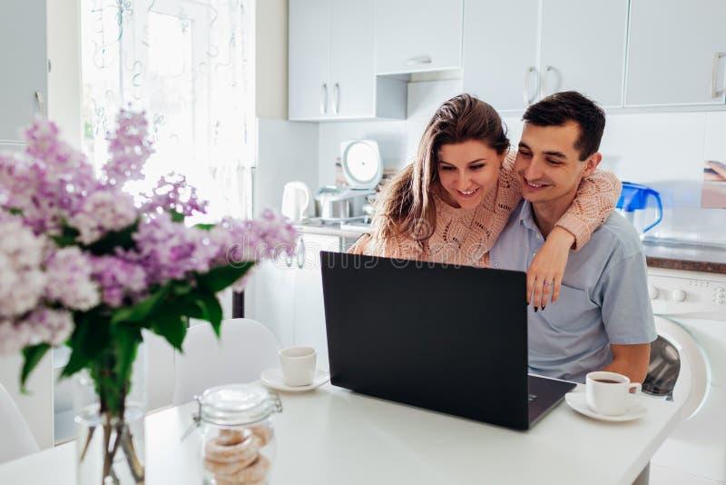 使用膝上型计算机的愉快的家庭夫妇,当食用咖啡在现代厨房时 年轻人和妇女检查社会网络新闻组 免版税库存照片