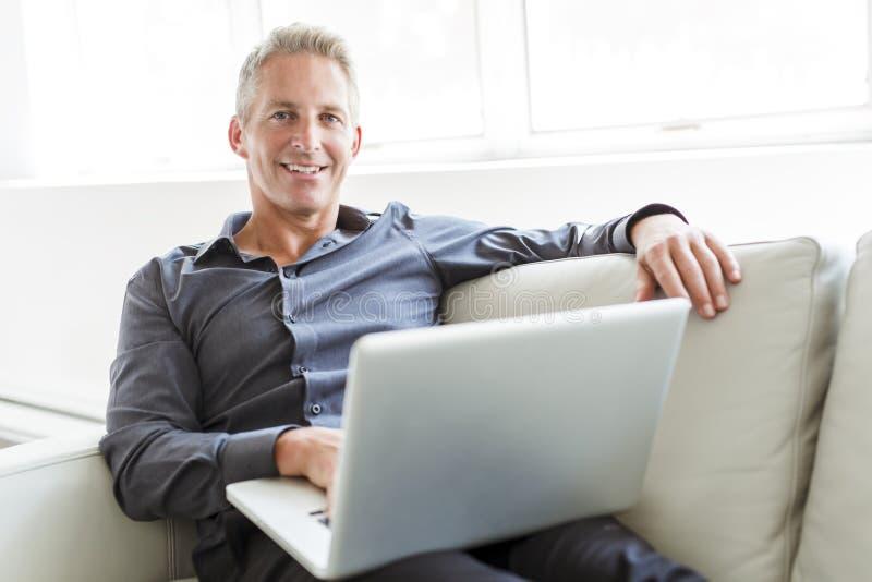 使用膝上型计算机的愉快的成熟人画象说谎在沙发在房子 库存照片