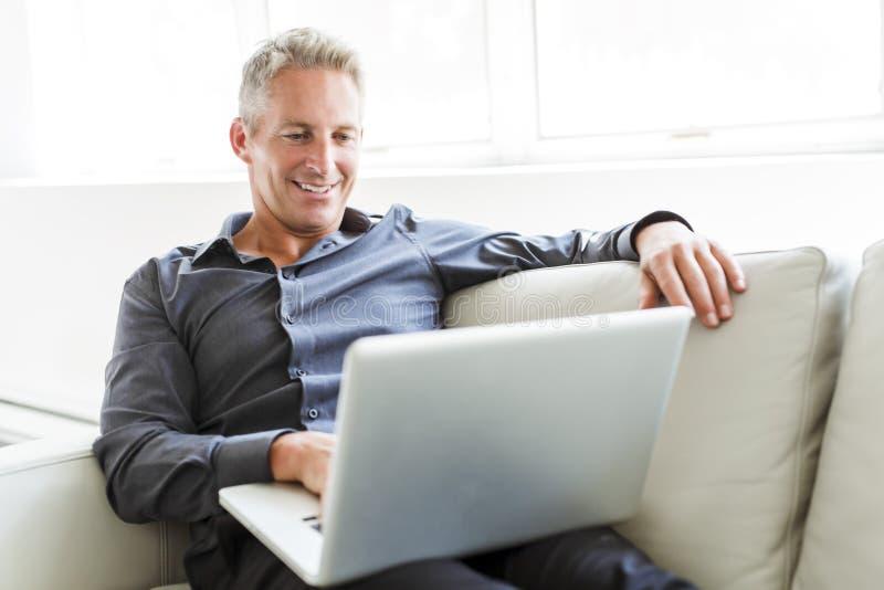 使用膝上型计算机的愉快的成熟人画象说谎在沙发在房子 库存图片