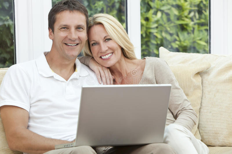 使用膝上型计算机的愉快的男人&妇女夫妇在家 库存照片