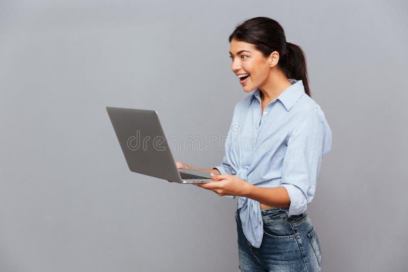 使用膝上型计算机的愉快的美丽的激动的妇女 免版税库存图片