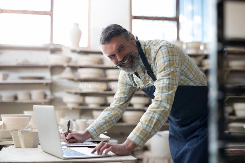 使用膝上型计算机的愉快的陶瓷工和微笑对照相机 免版税库存照片