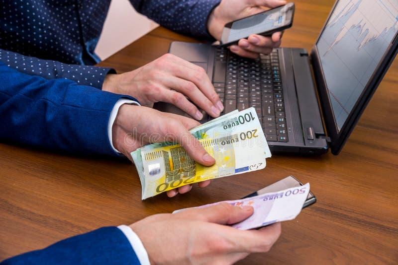 使用膝上型计算机的成功的年轻人待售 做金钱欧元的概念 库存图片