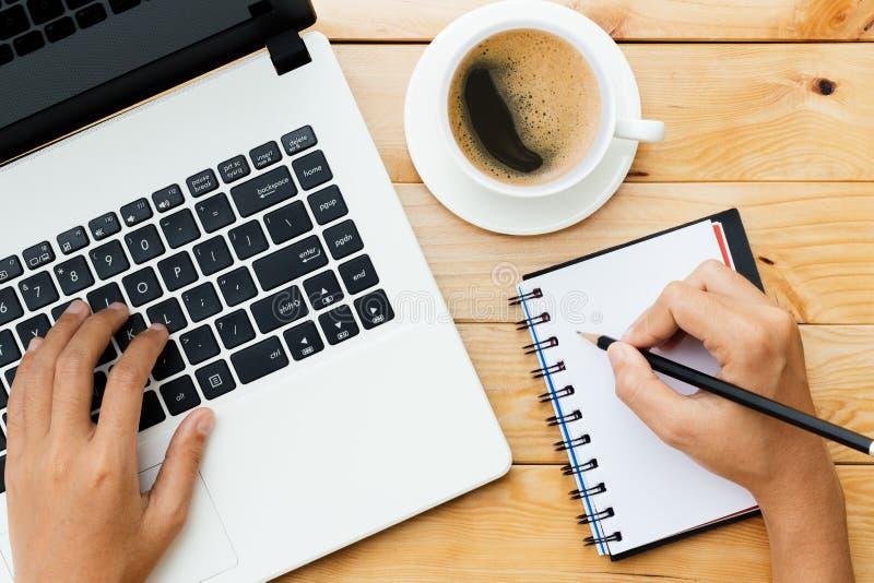 使用膝上型计算机的手和写笔记启发在木头的想法 免版税库存图片