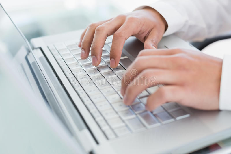 使用膝上型计算机的手在办公桌 免版税库存照片