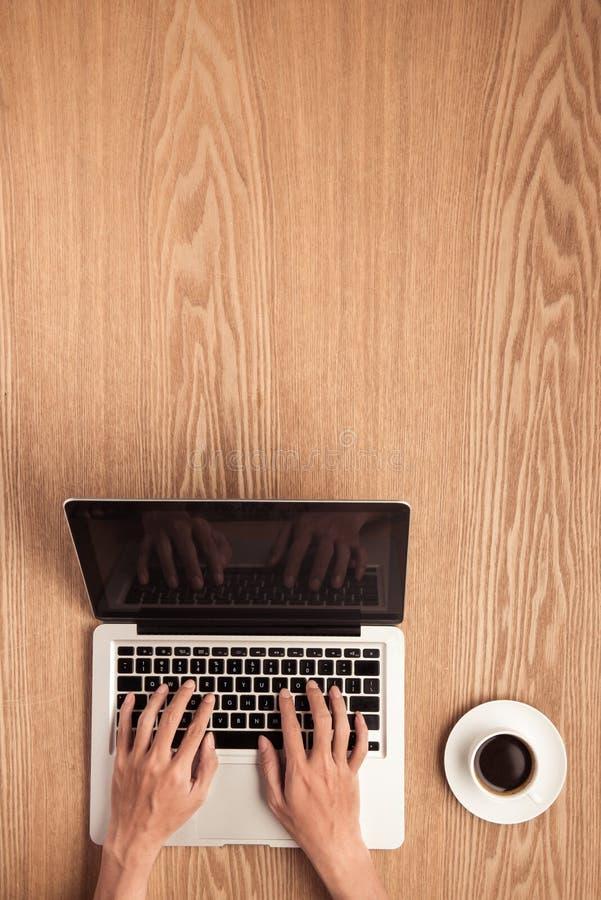 使用膝上型计算机的手有咖啡杯顶视图射击的 库存图片