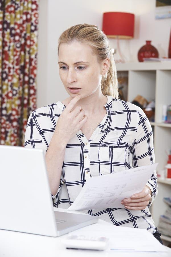 使用膝上型计算机的担心的妇女和回顾国内财务 免版税库存图片