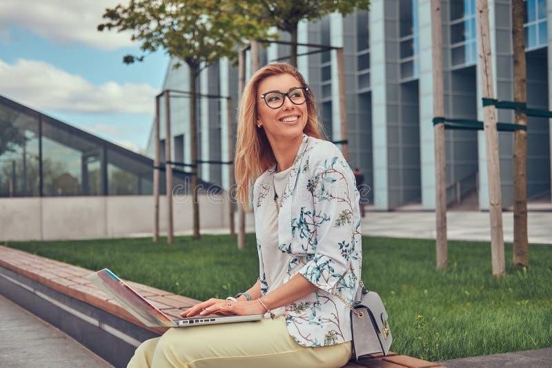 使用膝上型计算机的时髦的时尚博客作者为工作,当外面坐长凳反对摩天大楼时 免版税图库摄影