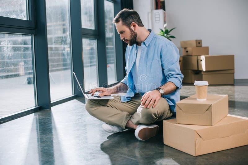使用膝上型计算机的有胡子的商人,当坐地板时 免版税图库摄影