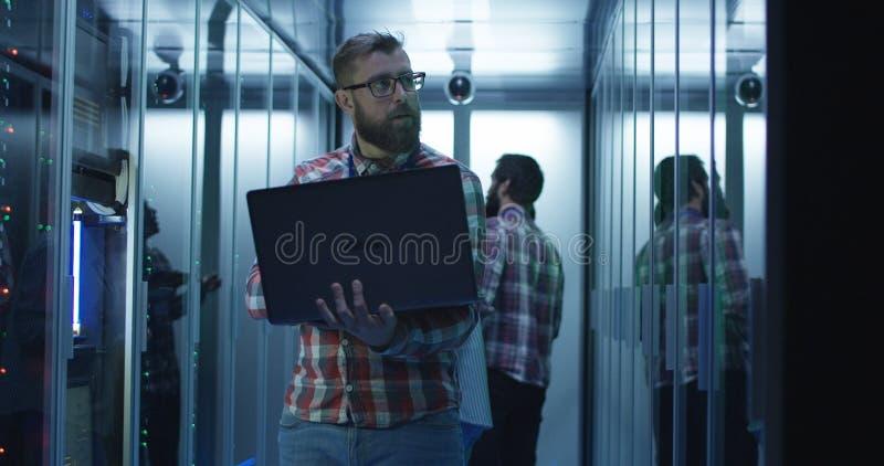 使用膝上型计算机的有胡子的IT工程师在服务器屋子里 图库摄影