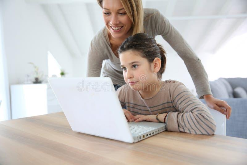使用膝上型计算机的母亲和女儿打录影电话 免版税库存图片