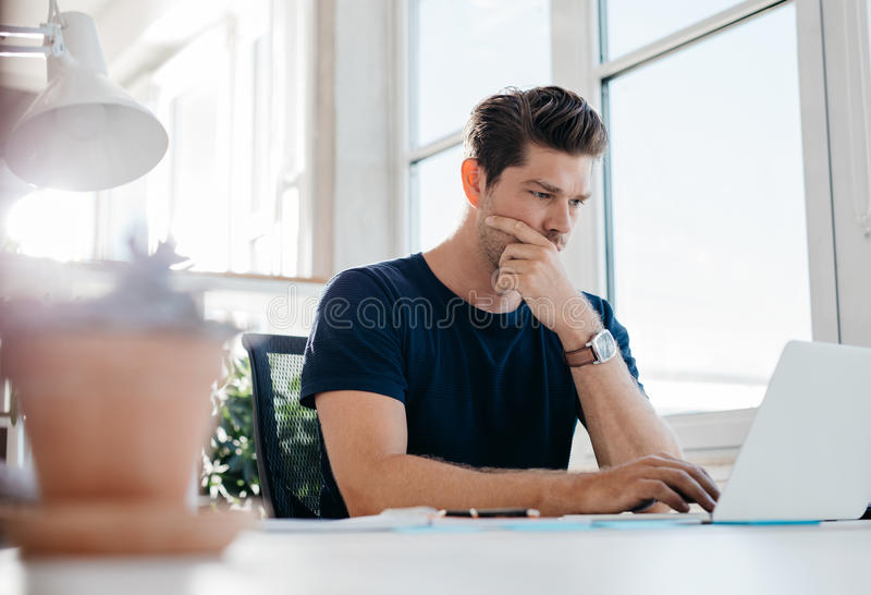 使用膝上型计算机的沉思幼小公执行委员在他的书桌 库存照片