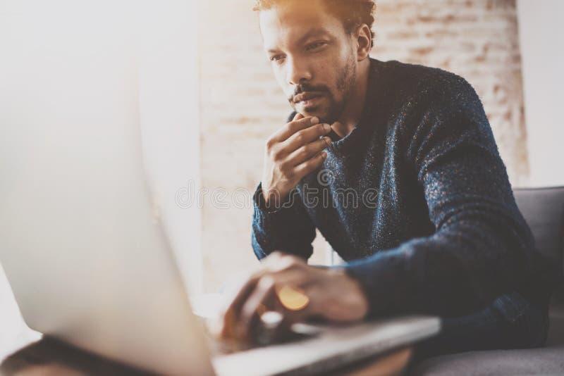使用膝上型计算机的沉思年轻非洲商人,当坐沙发在他的现代coworking的地方时 事务的概念 免版税库存照片