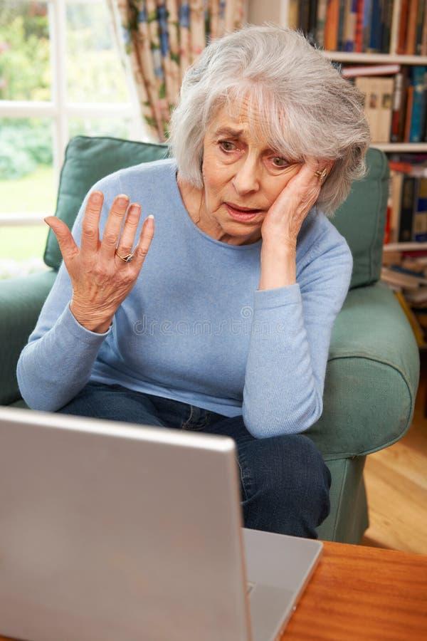 使用膝上型计算机的沮丧的资深妇女 免版税库存照片
